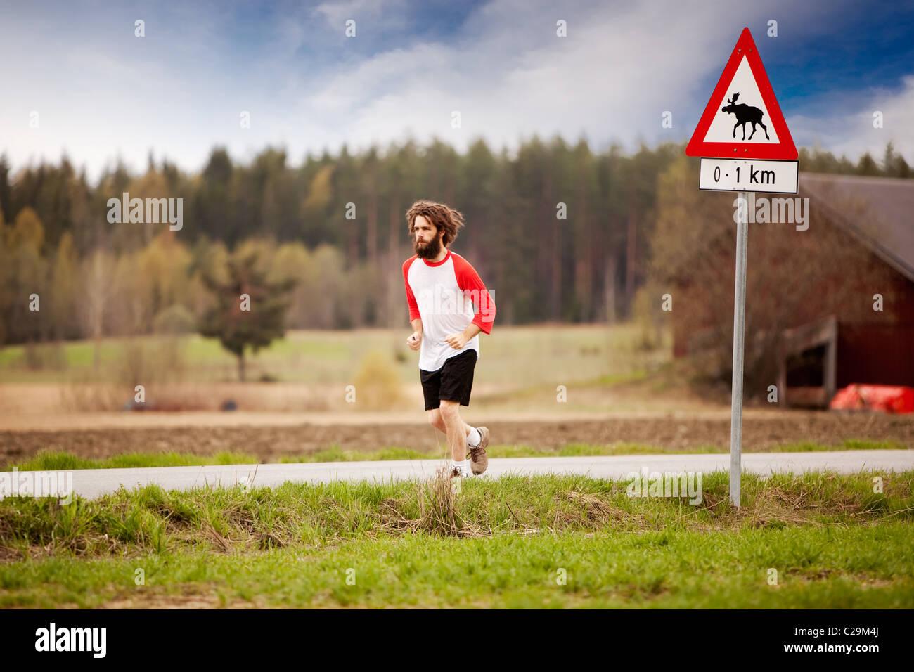 Un corridore con i capelli lunghi e la barba jogging nel paese Immagini Stock
