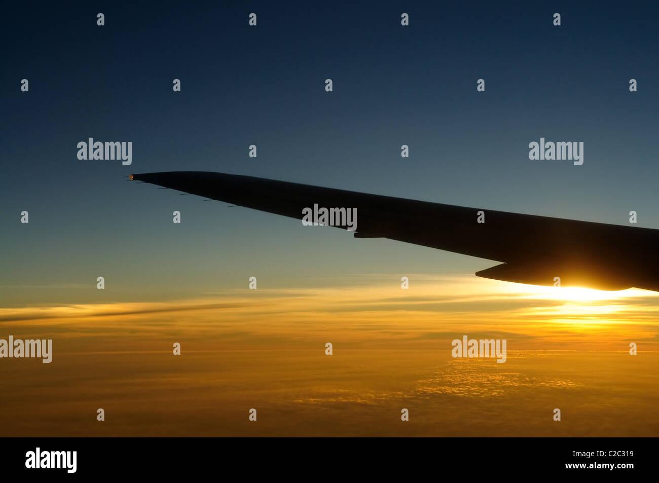 Tramonto sotto ala di aeroplano skyline Immagini Stock