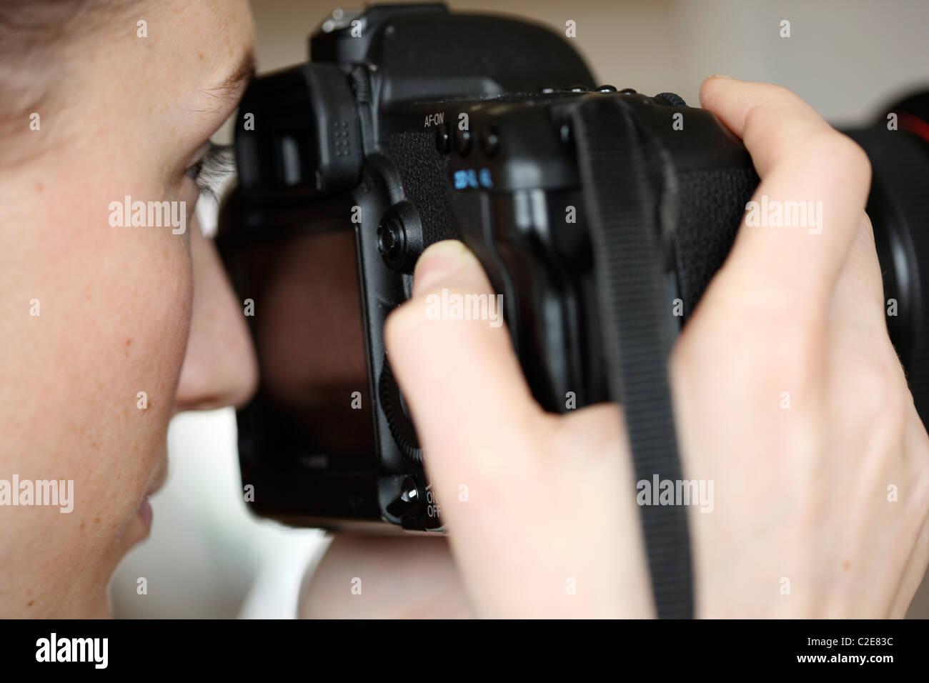Persona, femmina, guarda attraverso il mirino di una fotocamera reflex digitale. Foto Stock