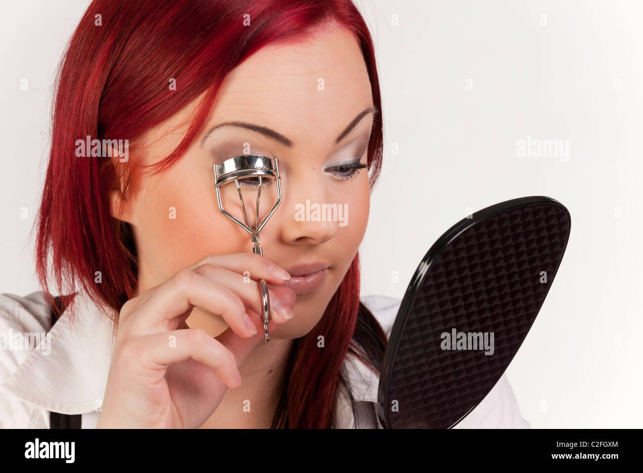 Una giovane donna di bellezza è tenuto lo stato di ciglia utilizzando arricciatore ciglia e tenendo la mano Immagini Stock