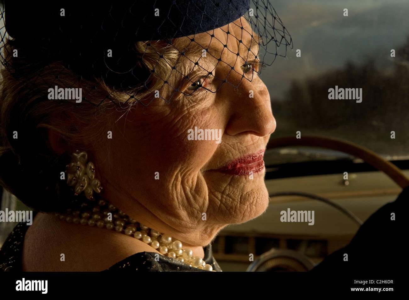 Senior donna matura è alla guida di un'auto d'epoca Immagini Stock