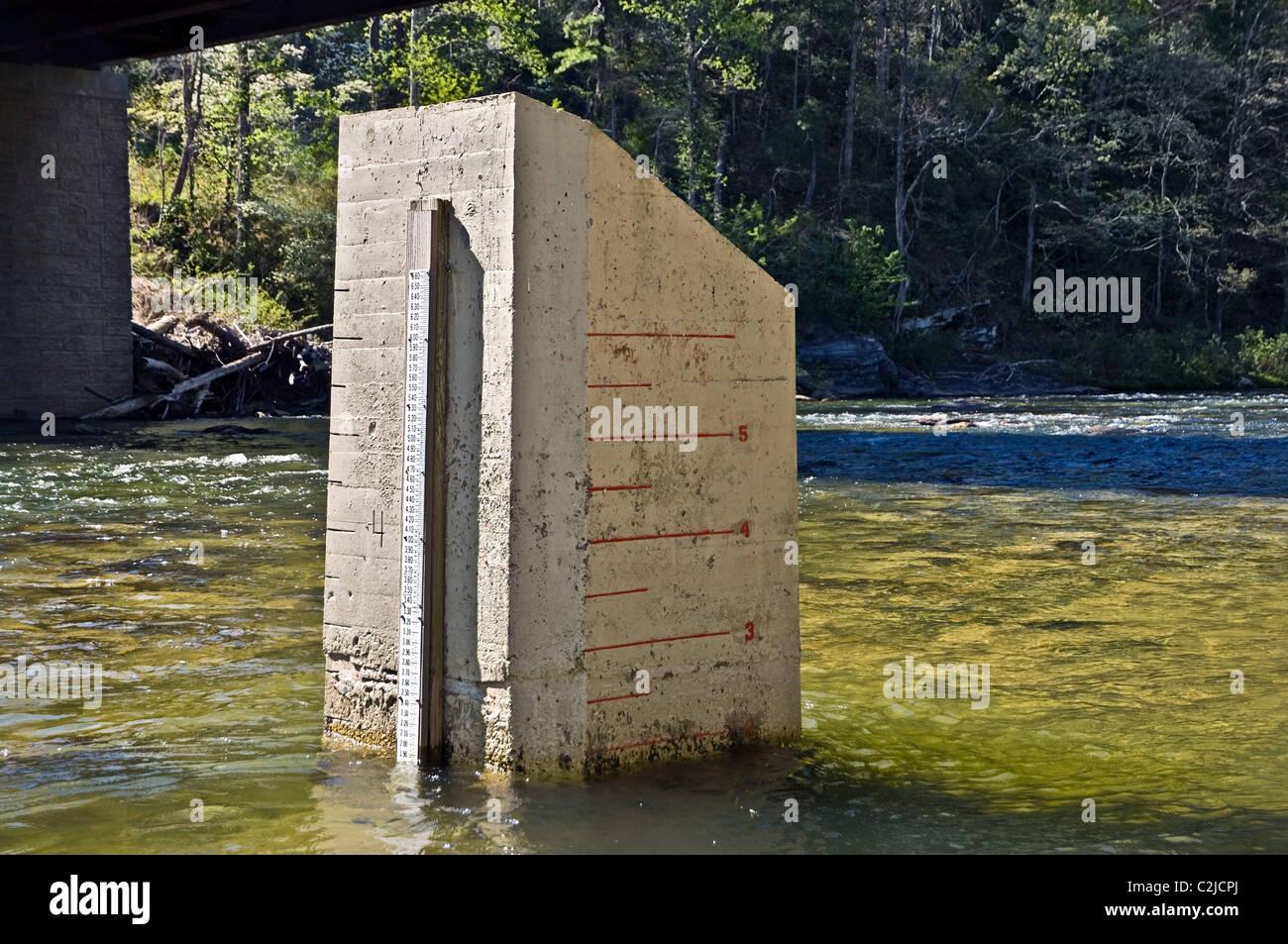 Un misuratore di acqua sui due lati di un blocco di calcestruzzo in un fiume. Utilizzato da kayakers e travi a vista. Immagini Stock