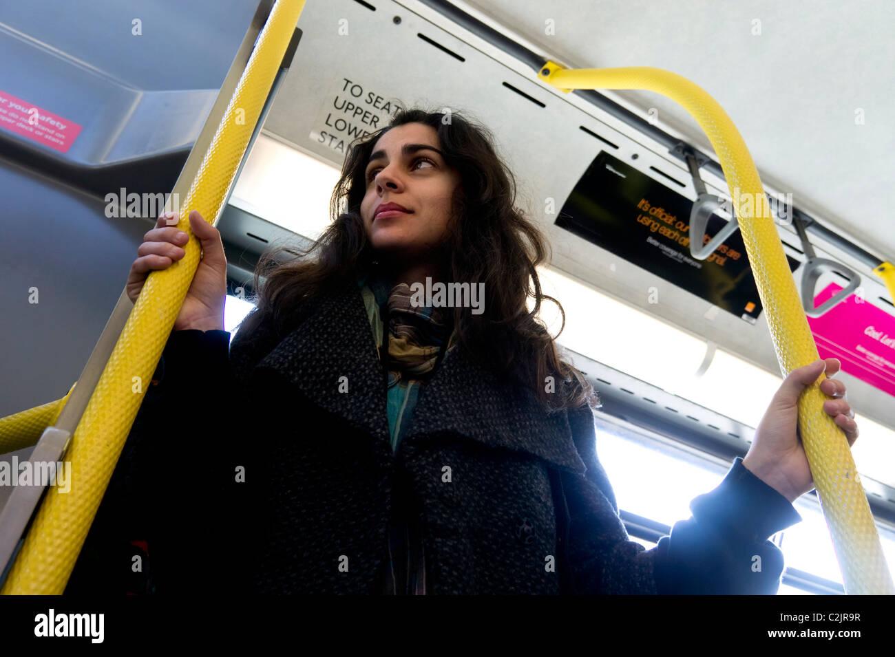 Basso angolo vista della giovane donna a cavallo di un autobus di LondraFoto Stock