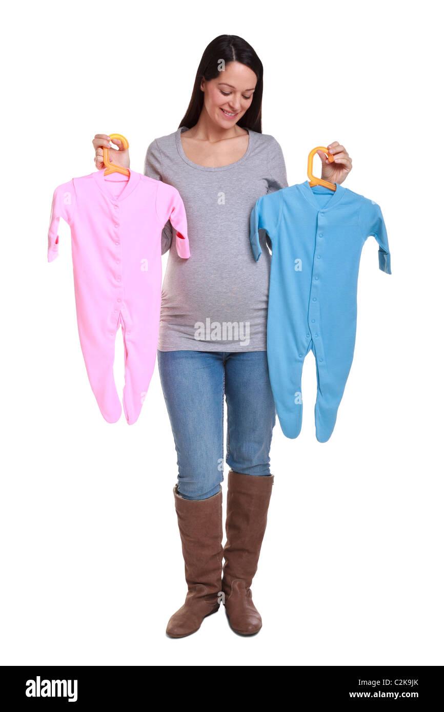 Foto di un attraente brunette donna che è di 32 settimane di gravidanza tenendo un rosa e azzurro baby crescere,isolato Foto Stock