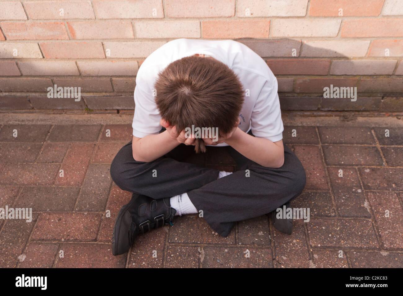 Un modello rilasciato la foto di un ragazzo di undici anni cercando premuto all'aperto con indosso la sua uniforme Foto Stock