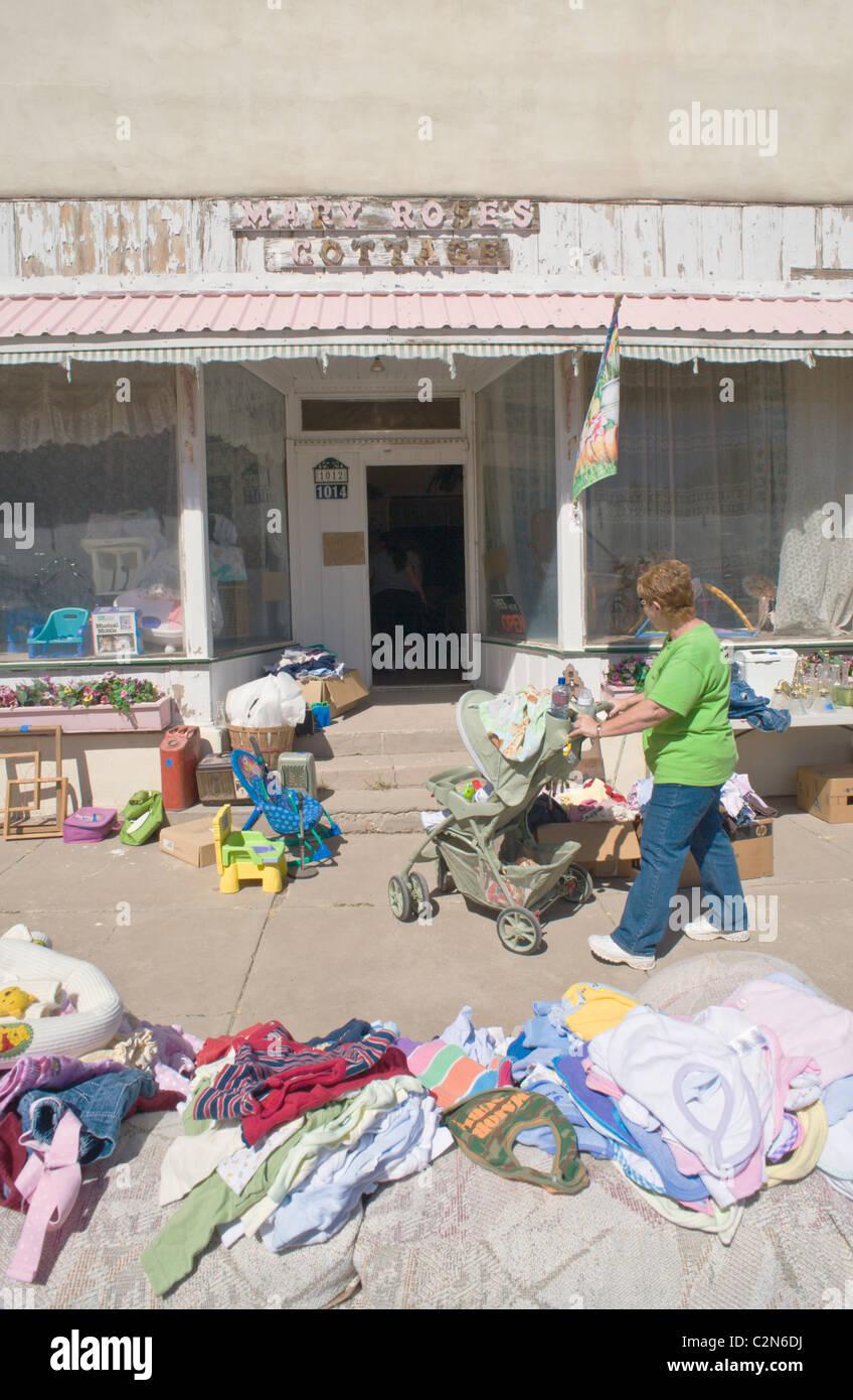 Una donna a spingere un passeggino (PRAM) guarda oltre le merci in un piccolo paese frugare vendita (accozzaglia Immagini Stock