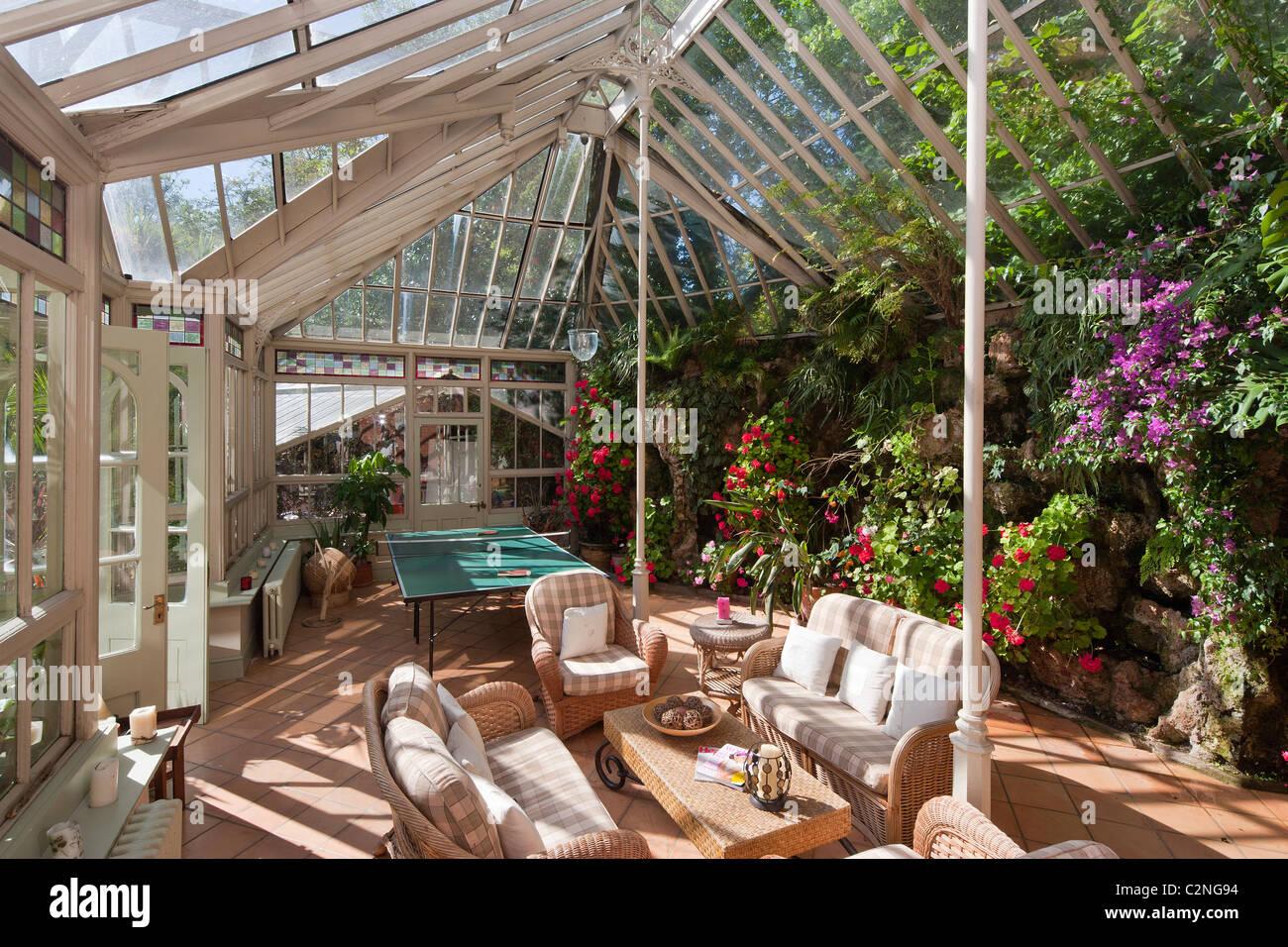 Aranciera e parete di tufo . Veranda con mobili da giardino Immagini Stock