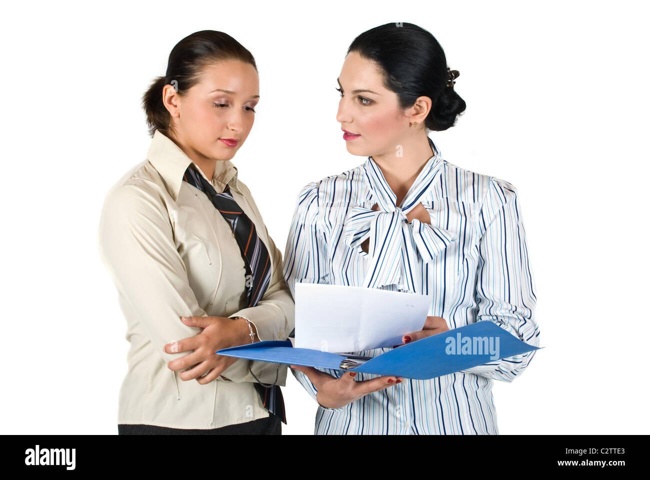 Due ragazze hanno una conversazione e guardano insieme in una cartella con le carte Immagini Stock