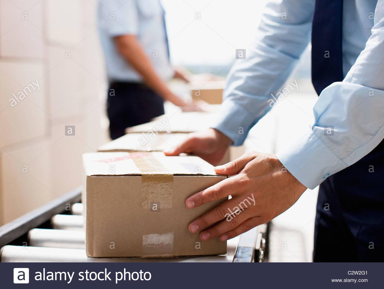 Lavoratore prendendo scatola dal nastro trasportatore nella zona di spedizione Immagini Stock