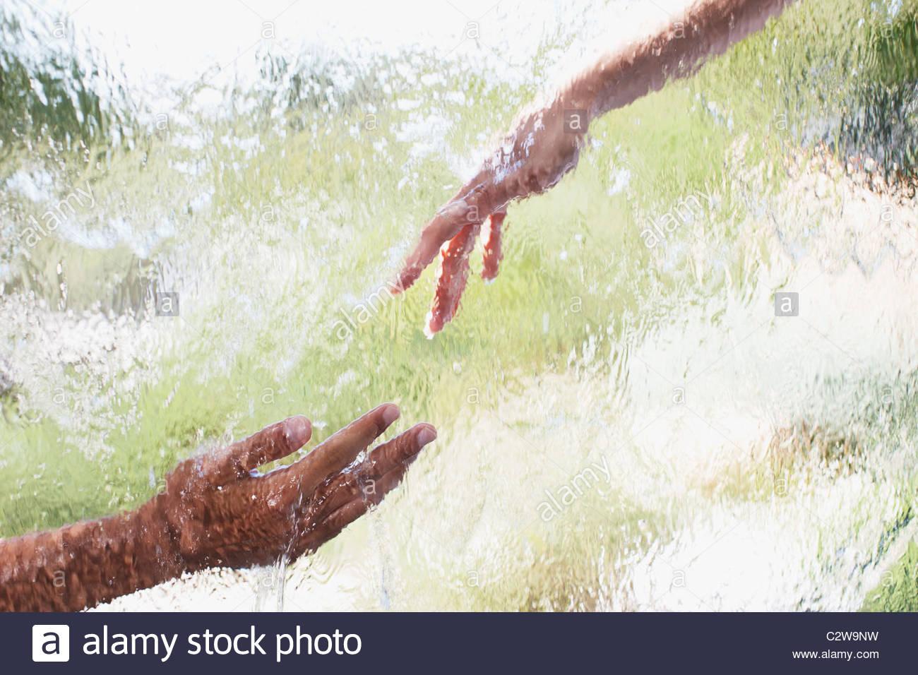 Due mani di raggiungere fuori dietro il vetro Foto Stock