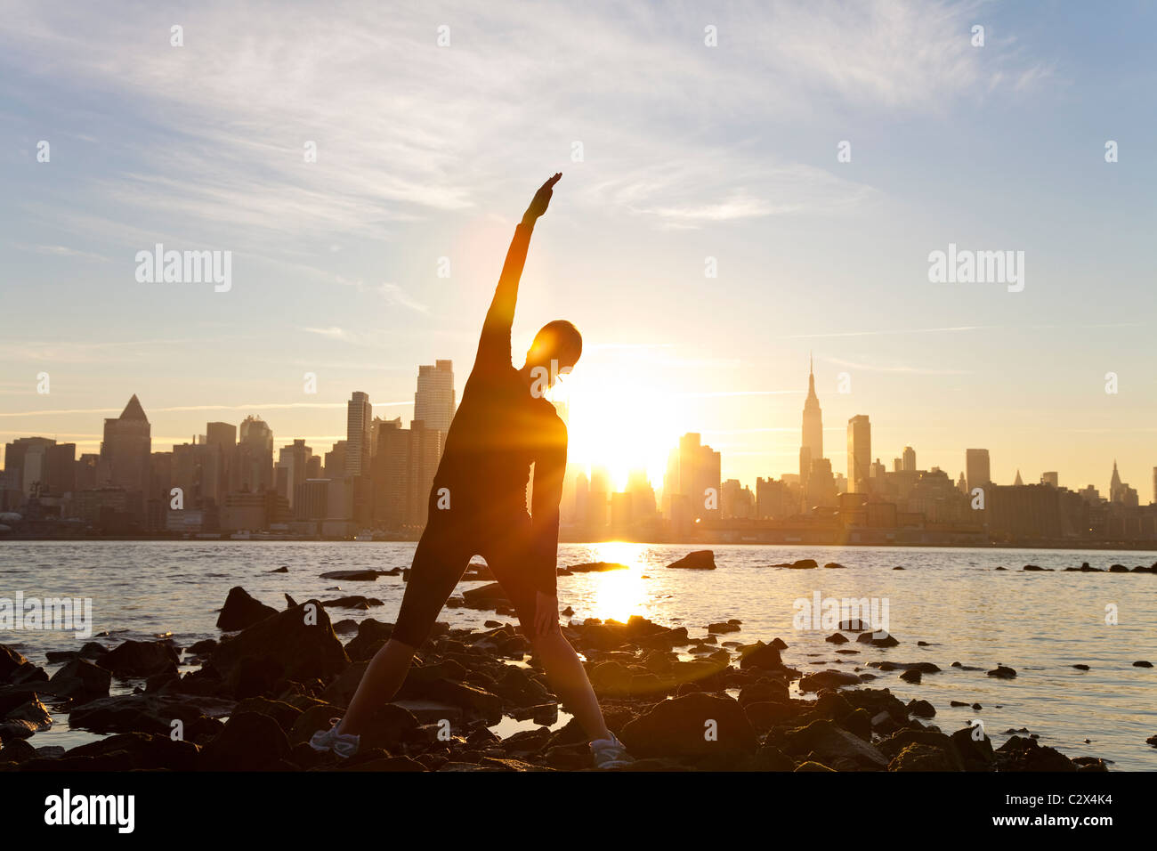 Una donna runner allungamento in una posizione di yoga nella parte anteriore dello skyline di Manhattan, New York City, Stati Uniti d'America, all'alba sunrise. Foto Stock