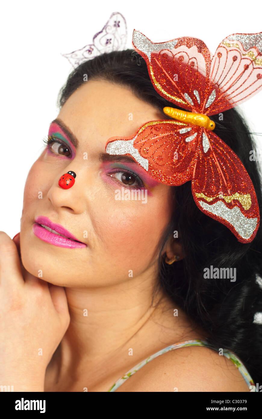 ritratto di donna di bellezza viso in semi profilo con grande farfalla nei capelli e ladybug camminando sul naso isolato su bianco