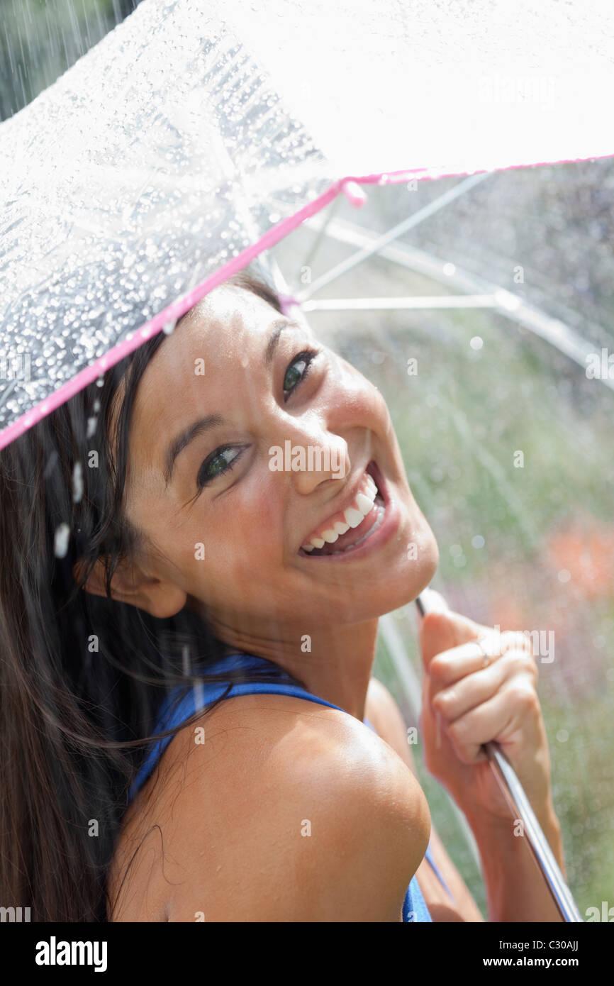 Bella giovane donna sorrisi verso la telecamera tenendo un ombrello sotto un getto di acqua. Colpo verticale. Immagini Stock
