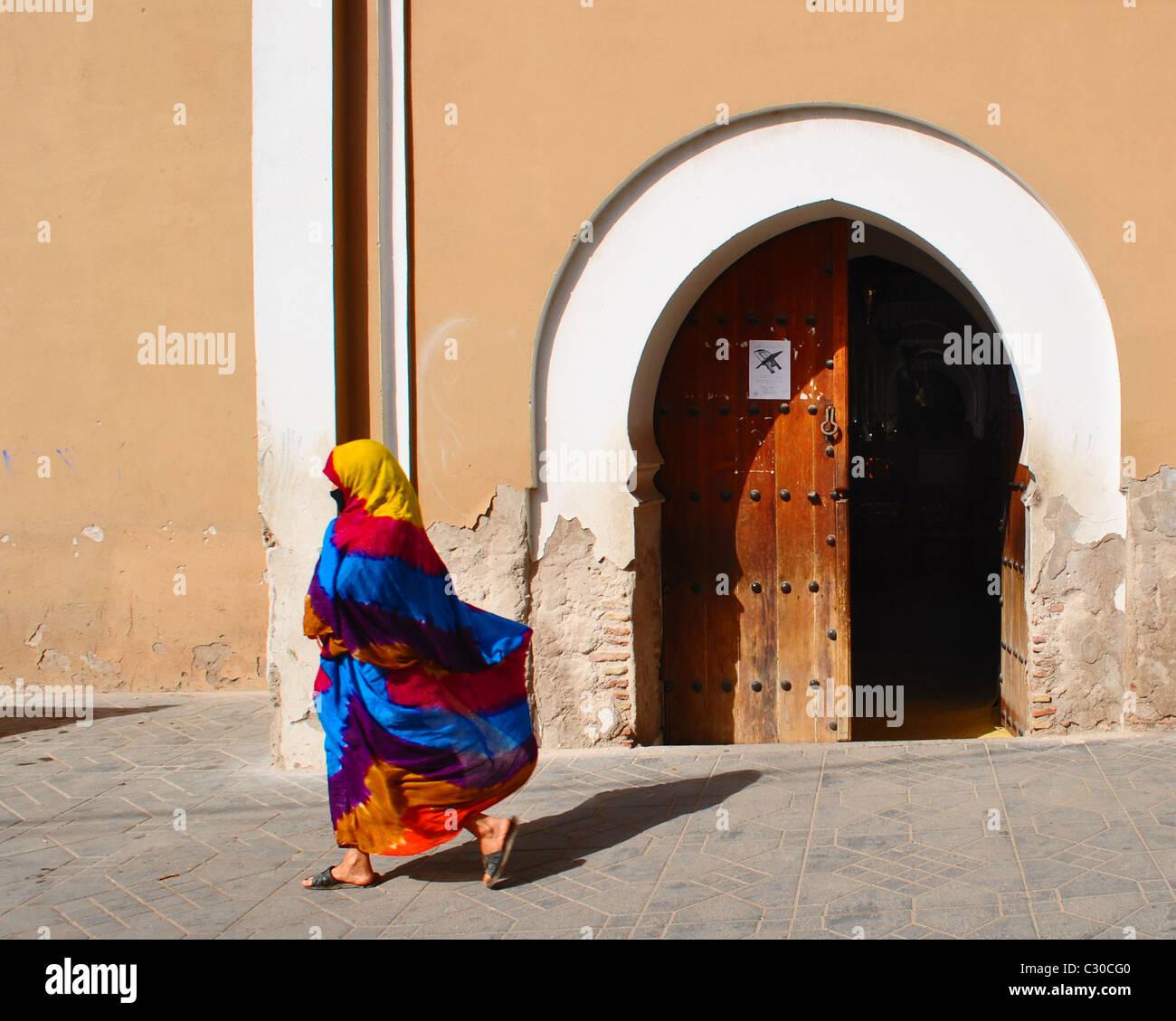 Donna con colori vivaci e fluenti jellaba oltrepassando una porta aperta in Taroudant, Marocco Immagini Stock
