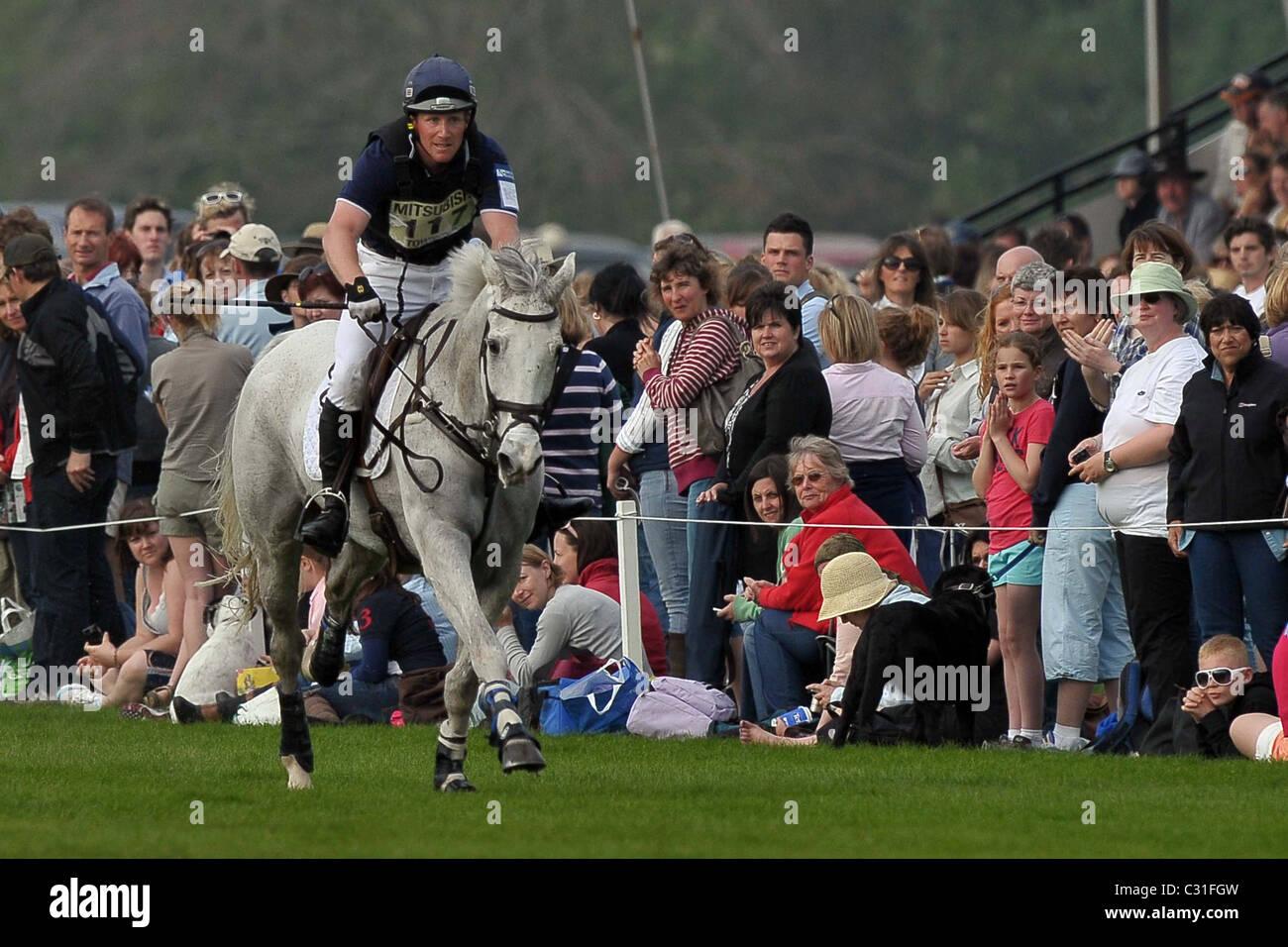 Oliver Townend equitazione CROCIERA ASHDALE MASTER galoppa verso il recinto 21 guardato dagli spettatori. Mitsubishi Immagini Stock