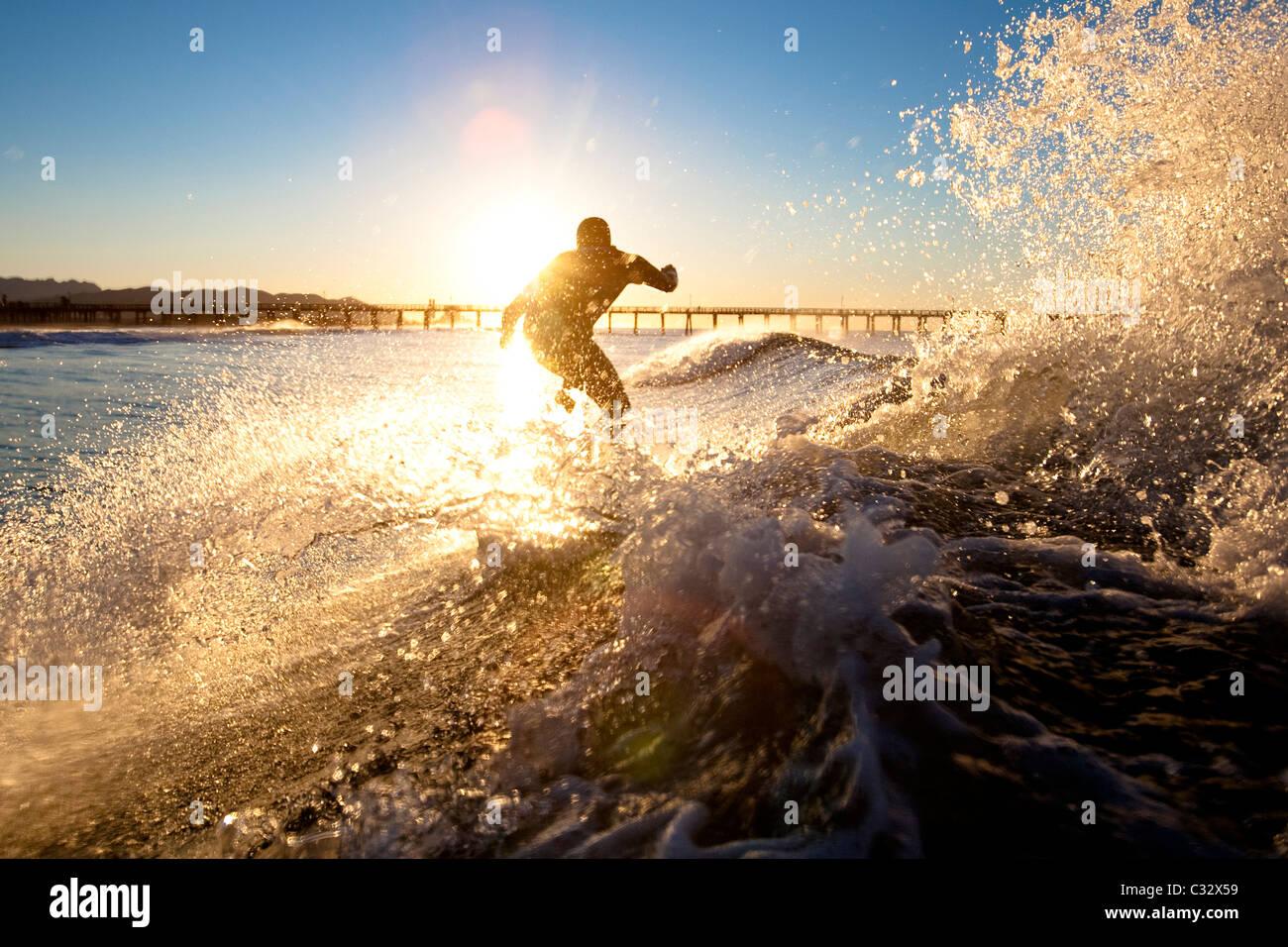Un surfista imposta per un'aria mentre cavalcate un'onda a Port Hueneme spiaggia nella città di Port Immagini Stock