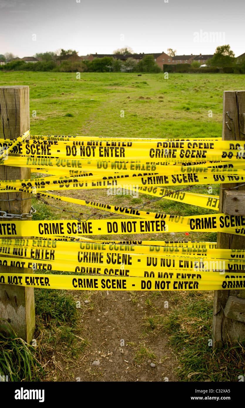 Il giallo della scena del crimine tape - non immettere - tra posti di legno con campo in background. Immagini Stock