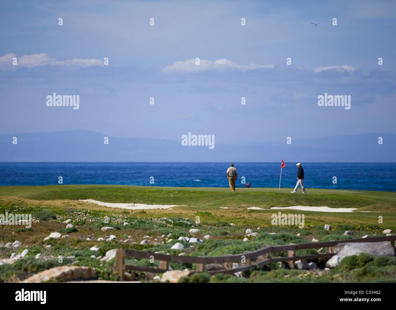 Gli amanti del golf sul putting green sul fronte oceano famoso campo di golf di Pebble Beach Immagini Stock