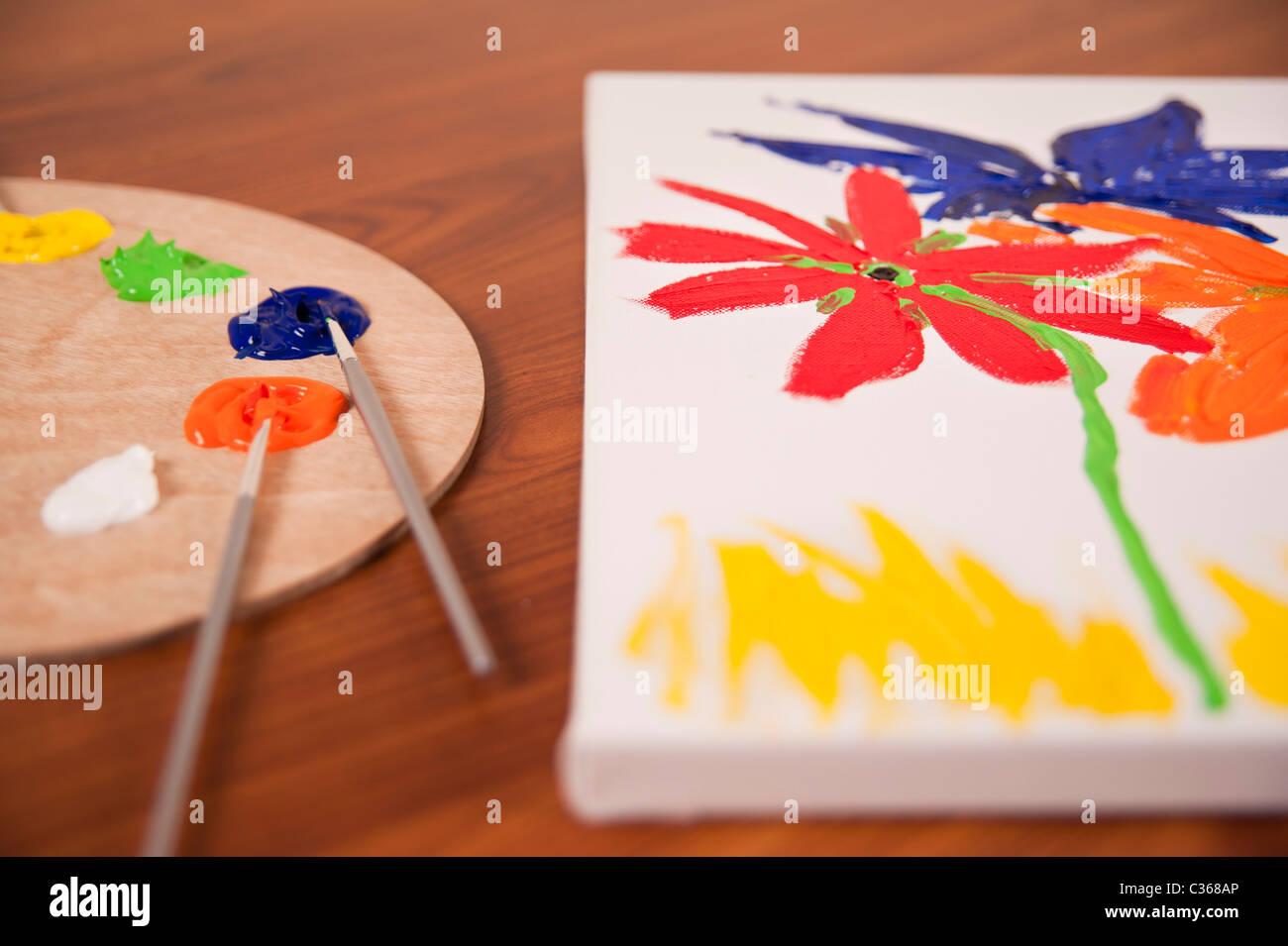 Una tavolozza di legno contenente un assortimento di spazzole e luminosi colori a olio si siede accanto a un mezzo Immagini Stock