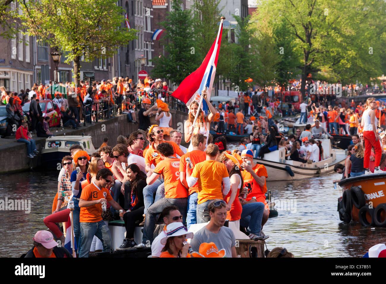 Kingsday, il compleanno del Re (Queensday Queen's Day) nella ragazza di Amsterdam sulla barca sventola bandiera Immagini Stock