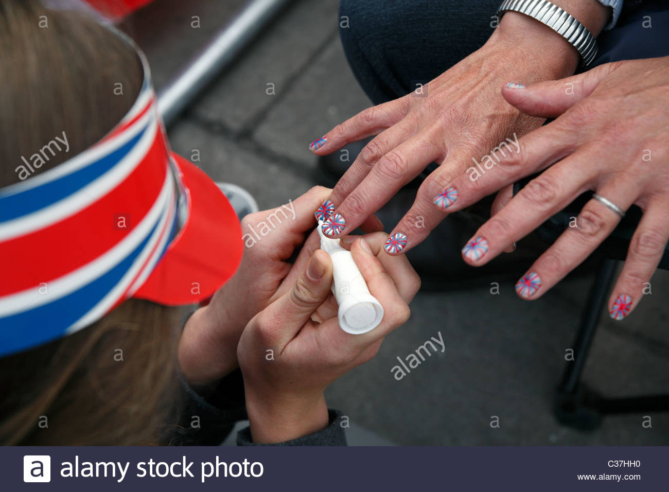 Una donna dipinge il suo amico le unghie con Union Jack Flag per il Royal Wedding del principe William e Kate Middleton Immagini Stock