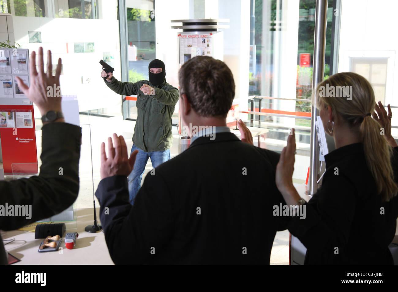 Esercizio di polizia. Rapina in banca. Bank Robber con una pistola tiene ostaggi in una banca. Foto Stock