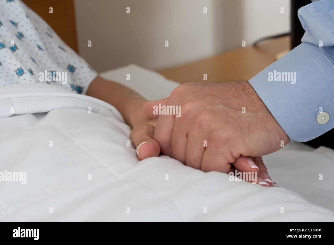 Close-up del giovane tenendo le mani durante il ricovero in ospedale Foto Stock