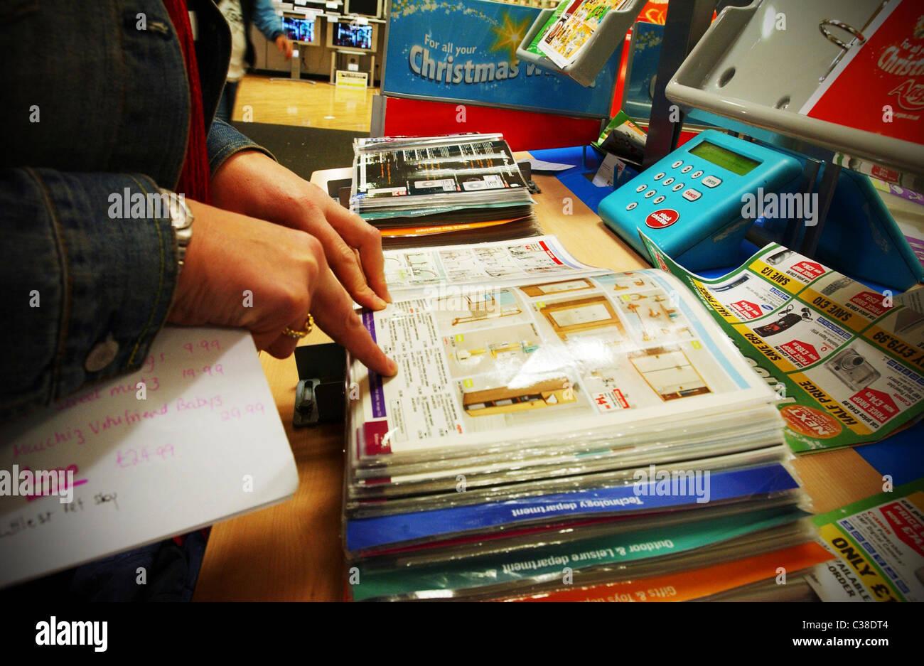 Una donna di controllare la descrizione del prodotto in un catalogo di Argos. Immagini Stock