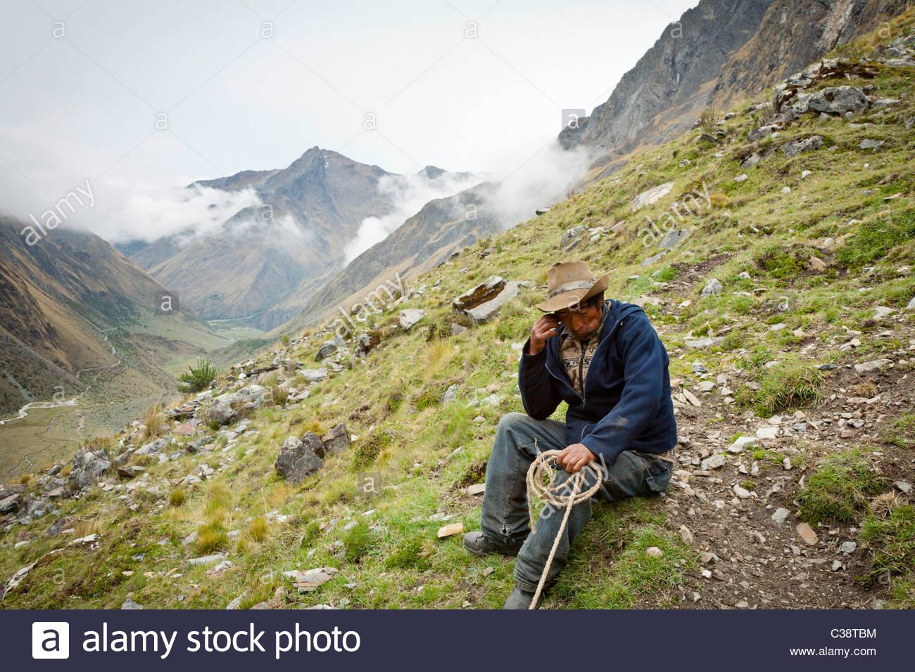 Locali di uomo che lavora come una guida e un mulo-driver sulla salita di Salkantay Pass lungo la coda di Salkantay, Immagini Stock