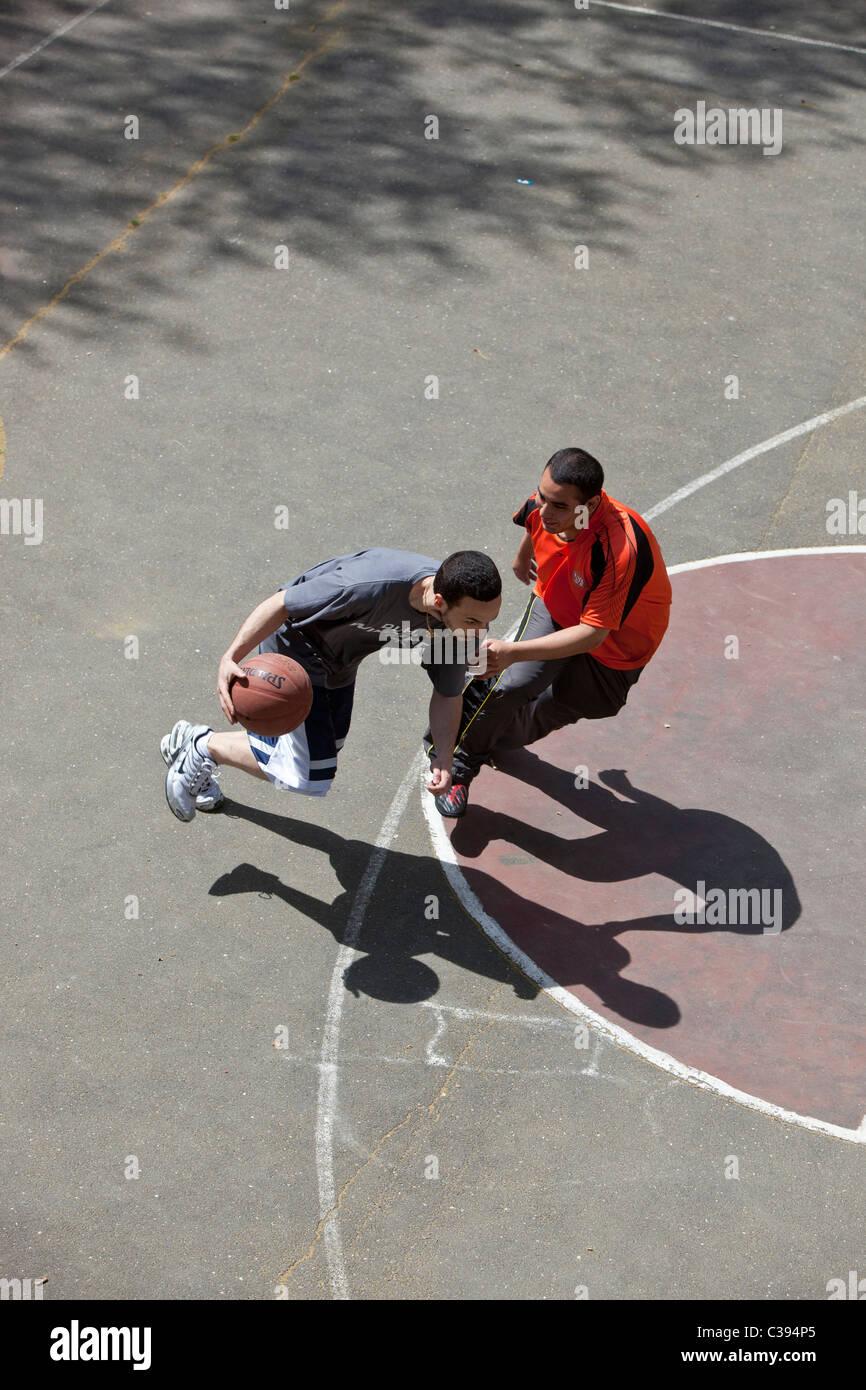 I giovani adulti giocando street basket in Riverside Park, New York City. Immagini Stock