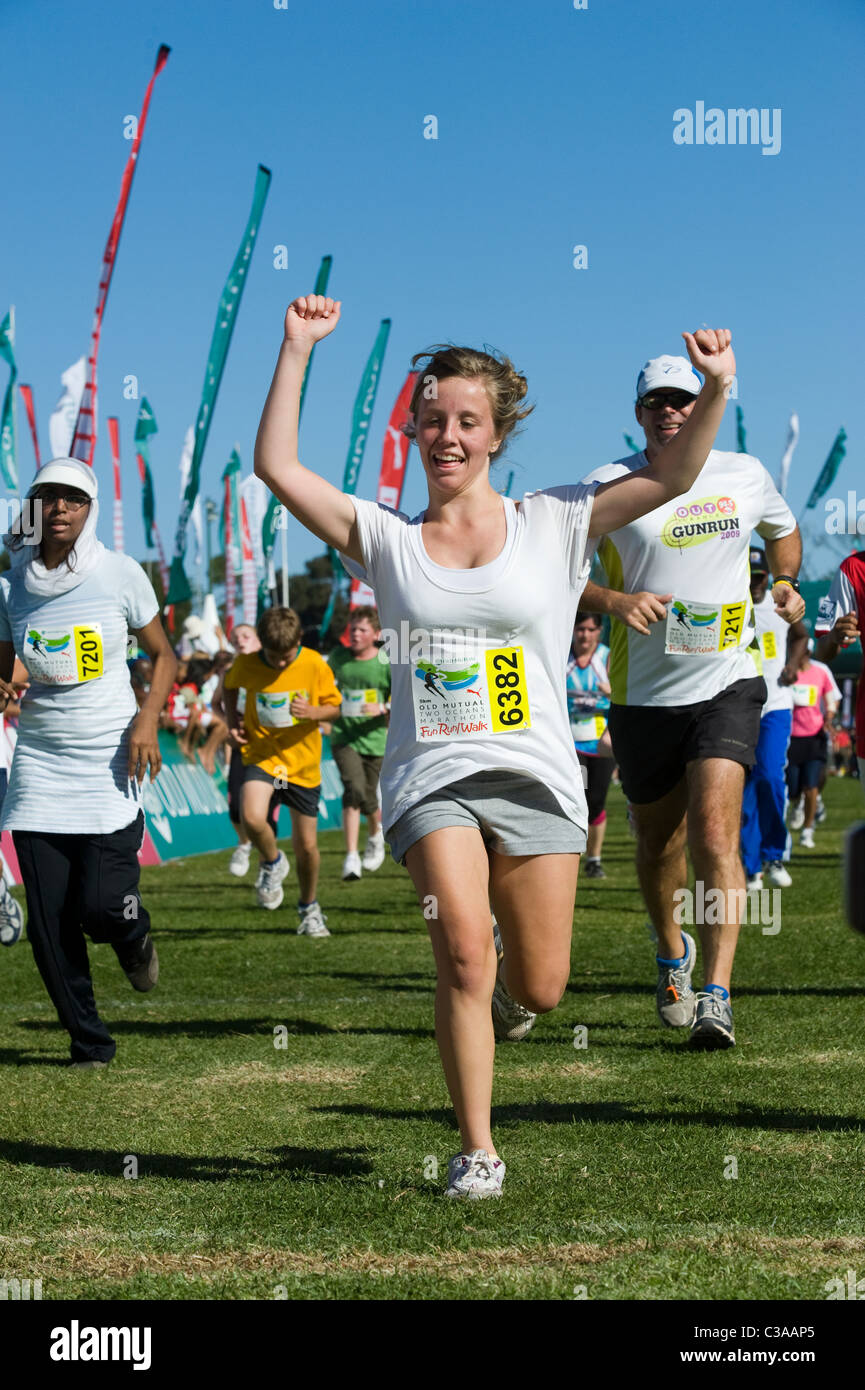 Runner festeggia al traguardo della 5km Fun Run, Two Oceans Marathon, Cape Town, Sud Africa Immagini Stock