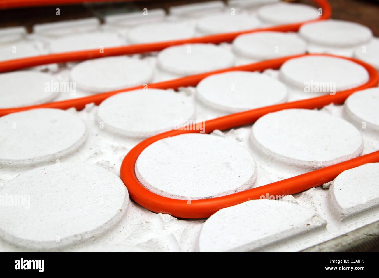 Pavimento radiante tubo tubo rosso curvo in cerchio bianco pattern Immagini Stock