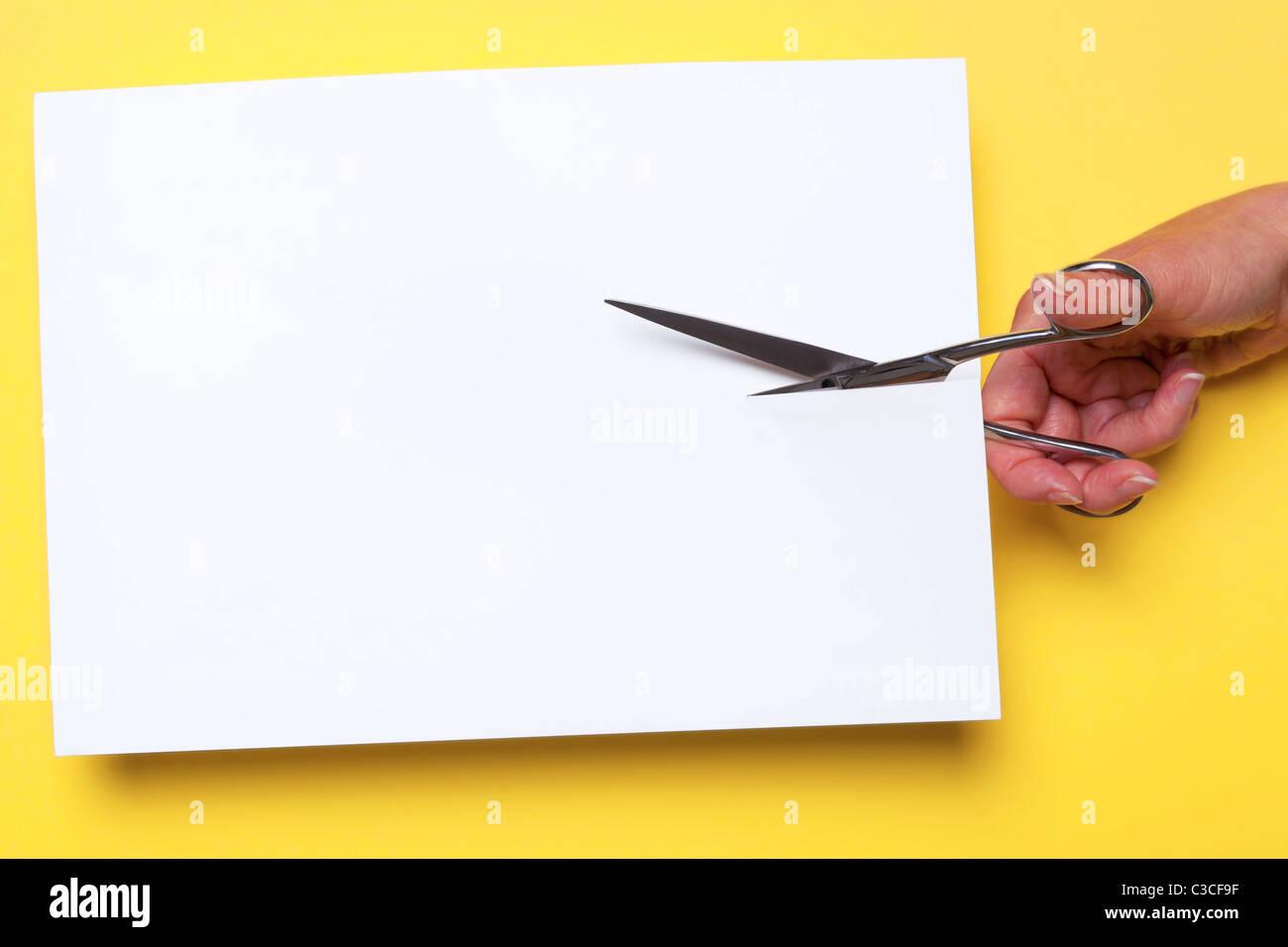Foto di un womans taglio a mano attraverso un pezzo di carta bianca Immagini Stock