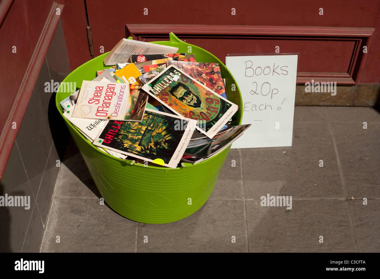 Una vasca di plastica piena di a buon mercato di seconda mano libri in brossura - 20p ciascuno, al di fuori di una Immagini Stock