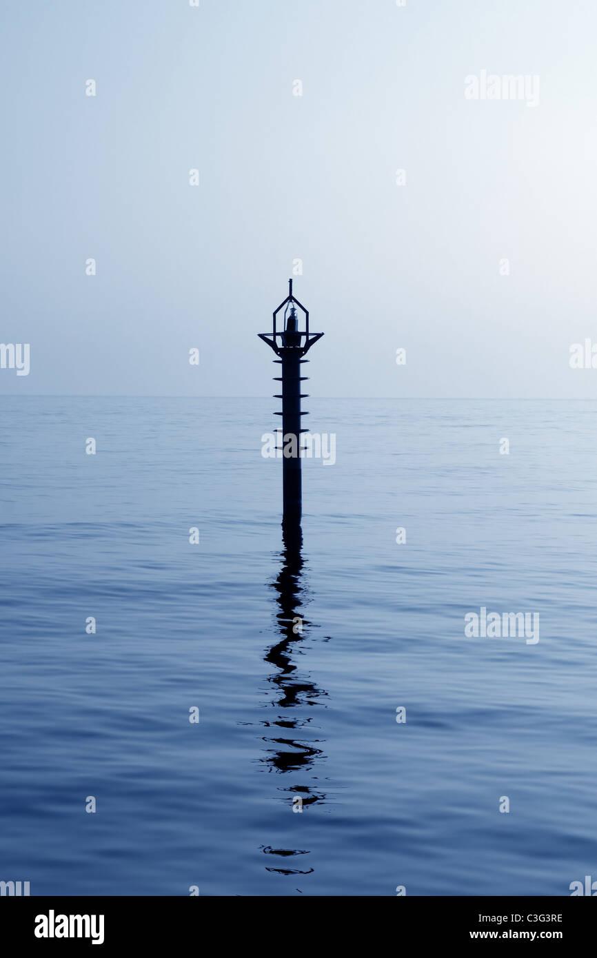 Indietro luce faro di navigazione nel blu mediterraneo acqua di mare la riflessione Immagini Stock