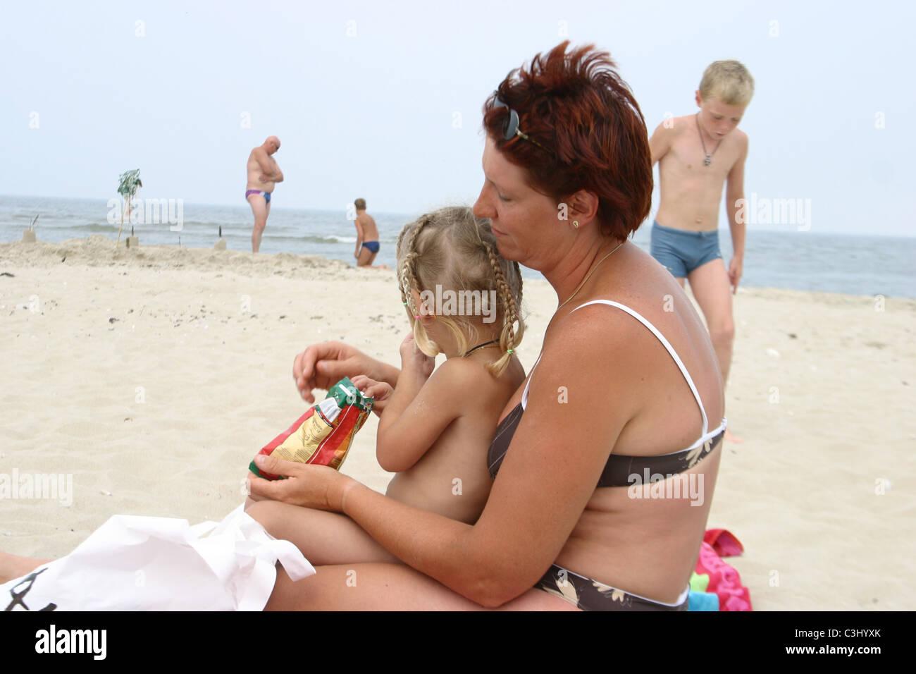 Donna adulta sovrappeso in bikini in spiaggia alimentazione di sua figlia il cibo spazzatura patatine in spiaggia. Immagini Stock