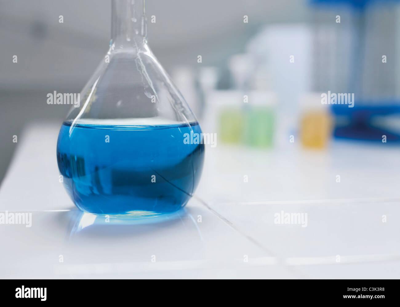 Pallone di vetro con fluido blu, close up Immagini Stock
