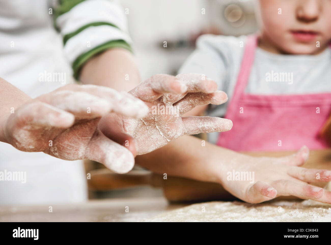 Germania, Colonia, un ragazzo e una ragazza di pasta di rotolamento sul piano di lavoro della cucina Immagini Stock