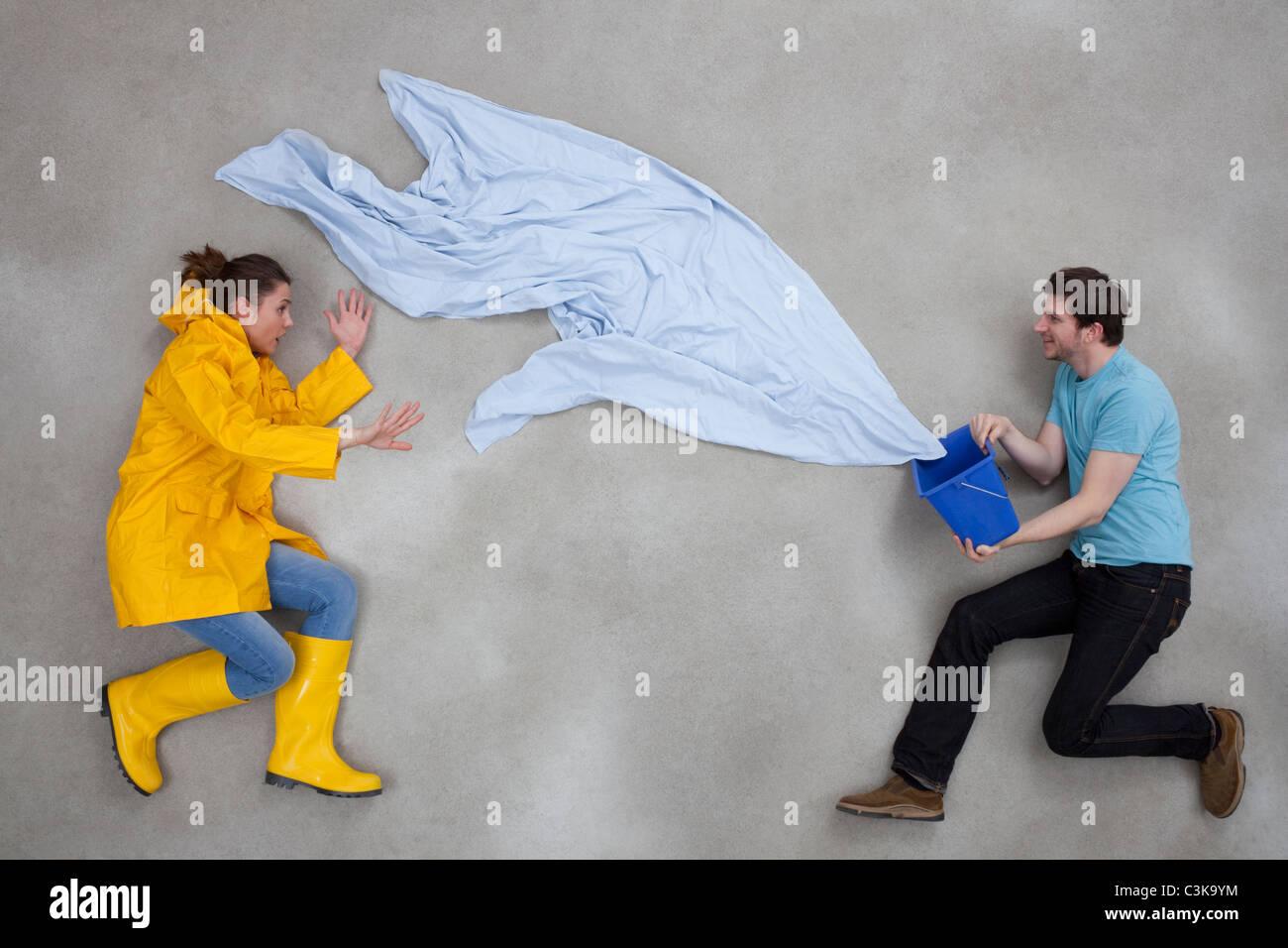 L'uomo schizzi secchio di acqua sulla donna Foto Stock