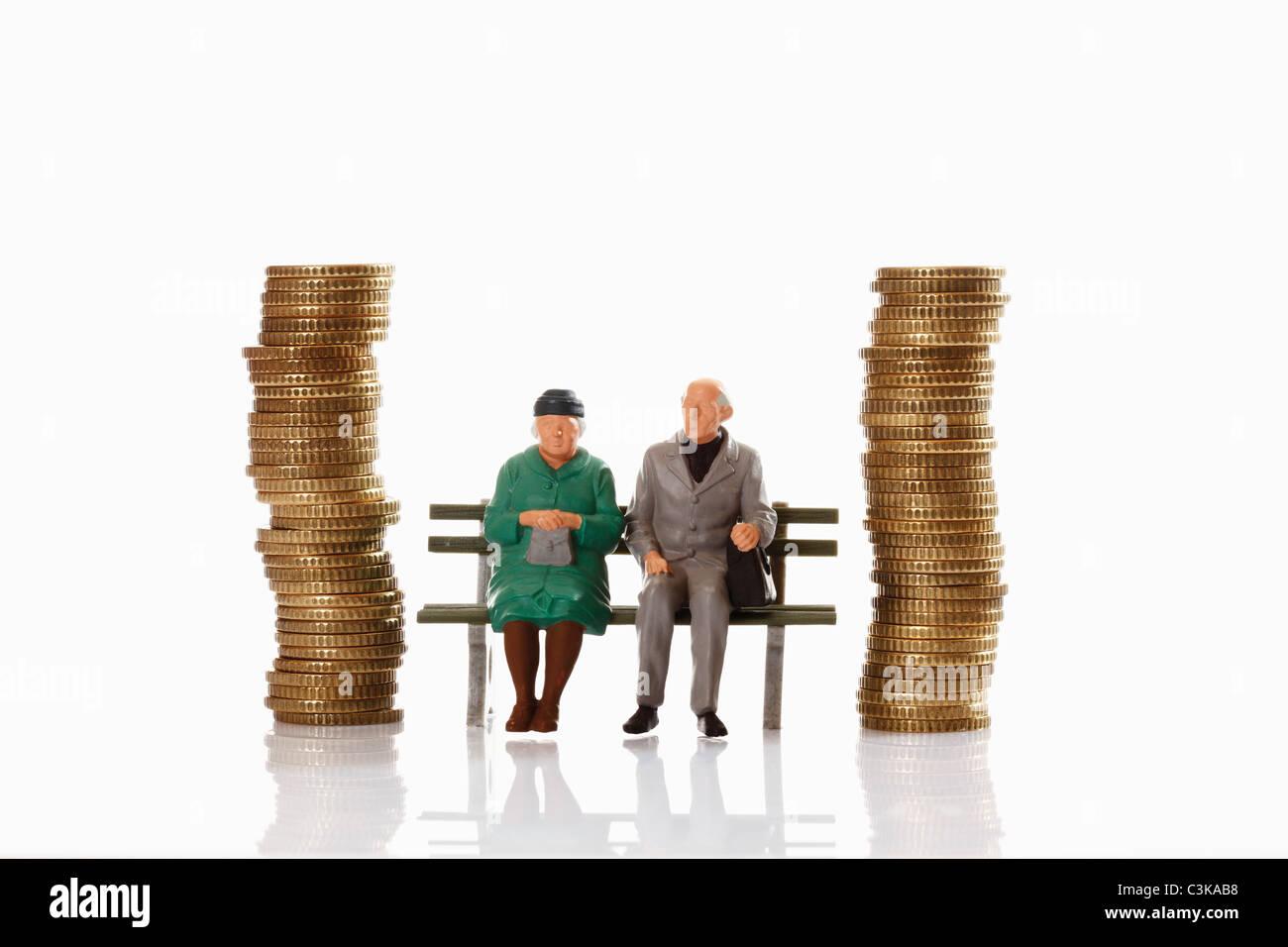 Figurine di vecchiaia pensionato seduto su un banco di lavoro tra pile di monete Immagini Stock