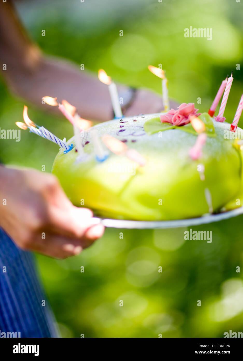 Donna che mantiene la torta di compleanno con candele accese, close-up Immagini Stock