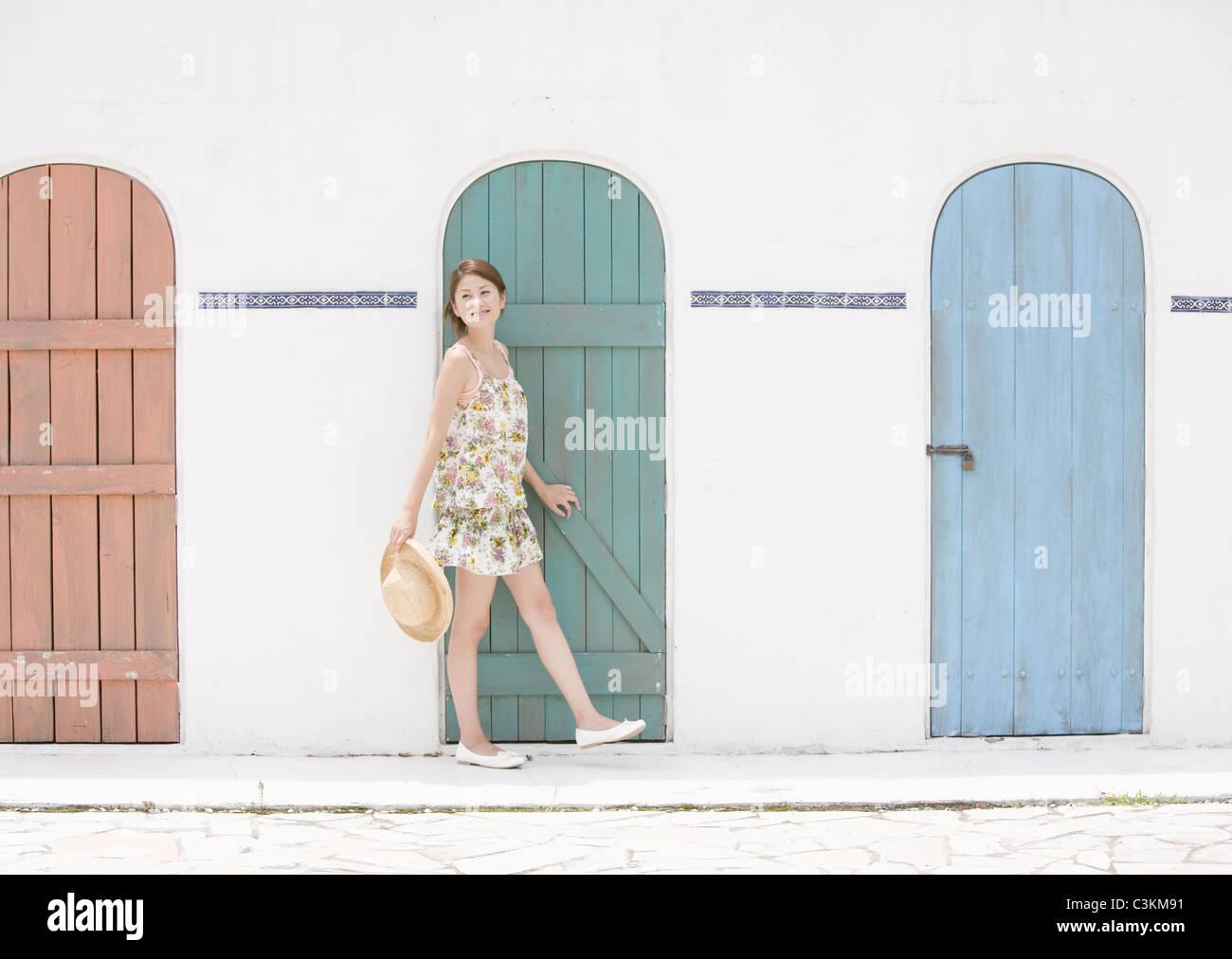 Giovane donna in piedi di fronte a porte Immagini Stock