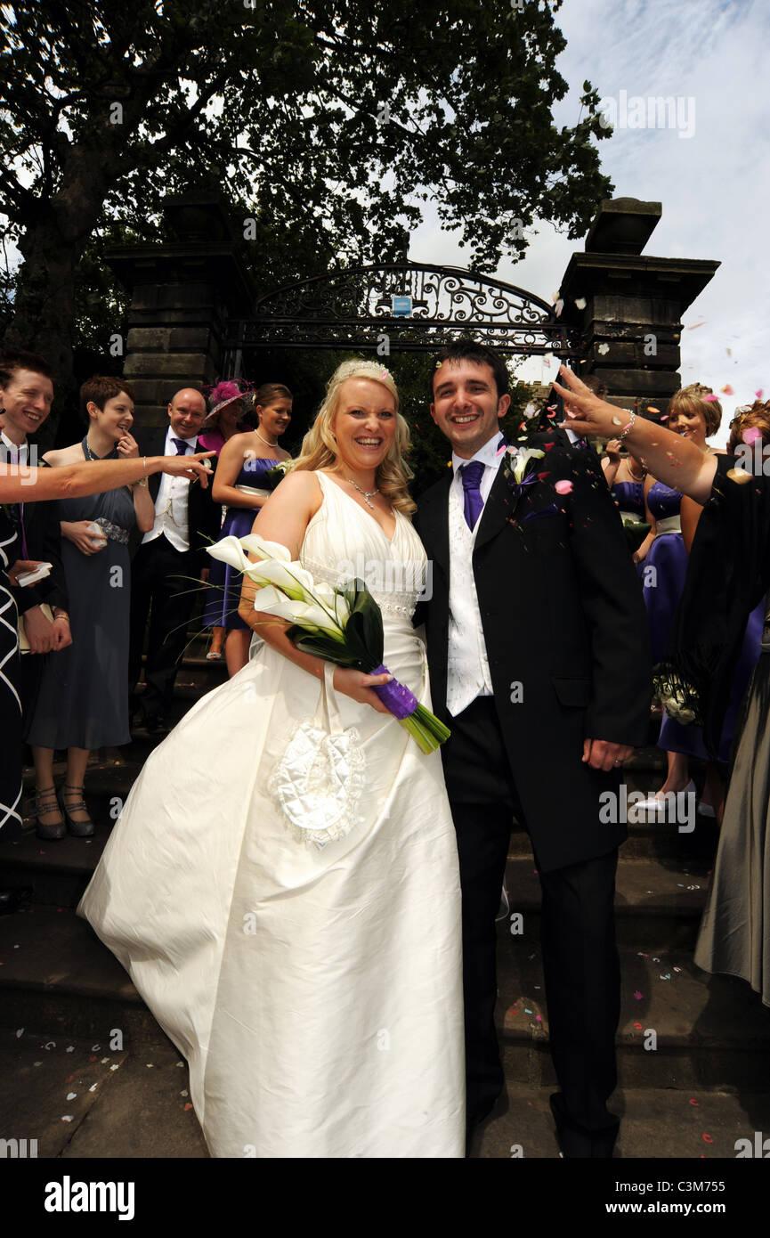 Coppia di novelli sposi hanno coriandoli gettati a loro al di fuori della chiesa dove si sono sposati. Immagini Stock