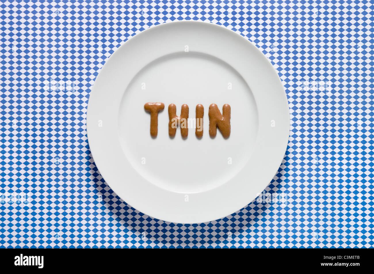 La parola scritta sottile con il pane russo sul piatto, close up Immagini Stock