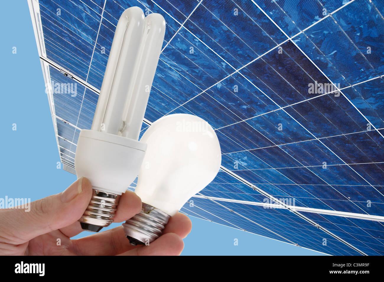 Mano umana tenendo luce a risparmio energetico, lampadina contro il pannello solare, vicino. Immagini Stock