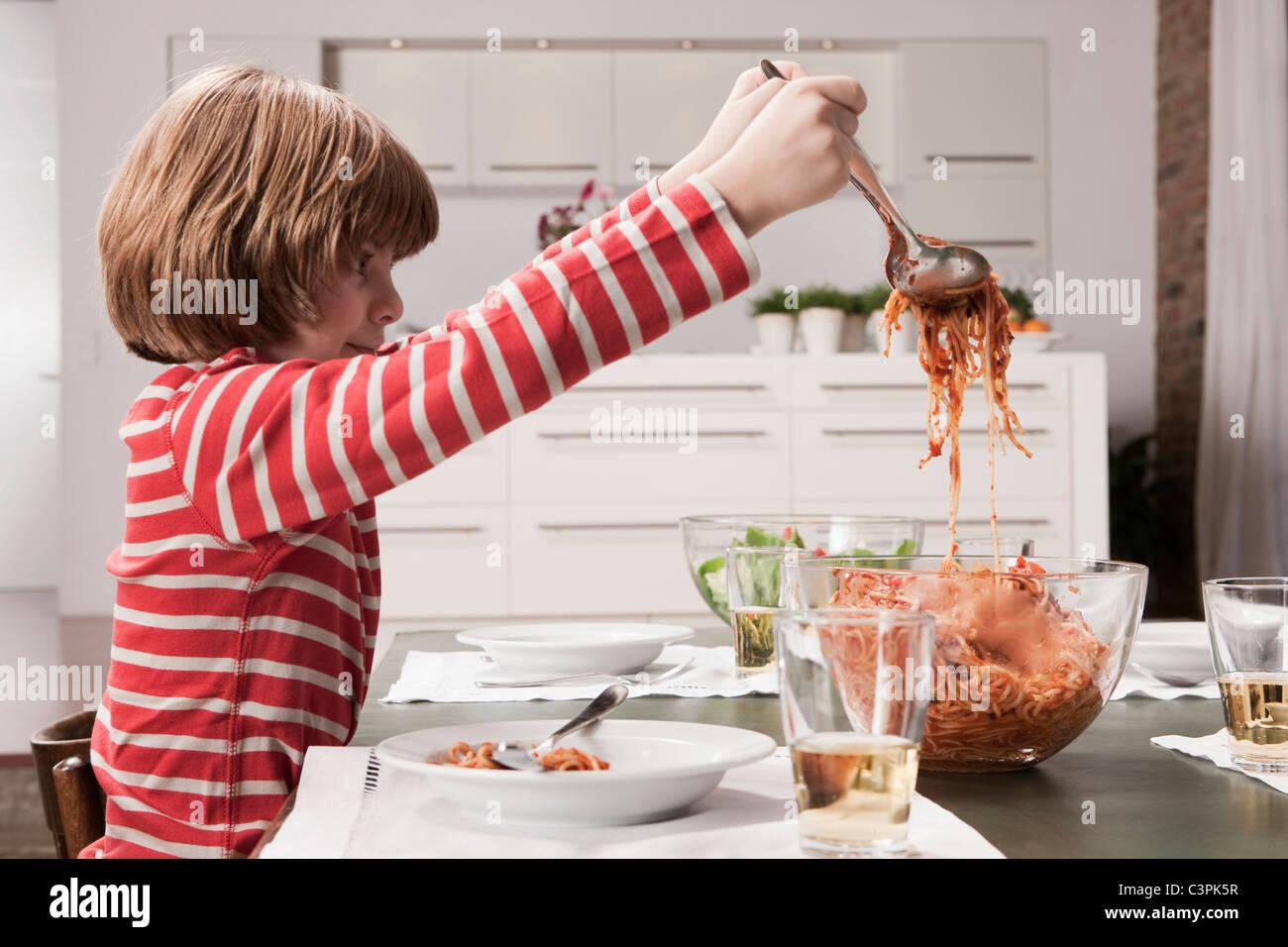 Germania, Colonia, ragazzo (6-7) che servono spaghetti, vista laterale Immagini Stock