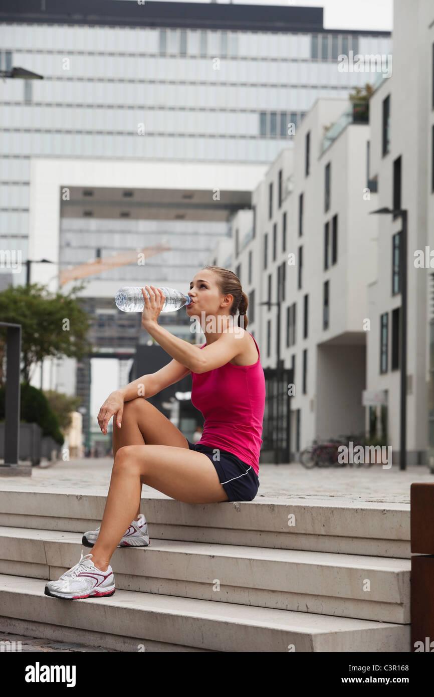 Germania, Colonia, giovane donna di bere acqua da bottiglie di acqua Immagini Stock