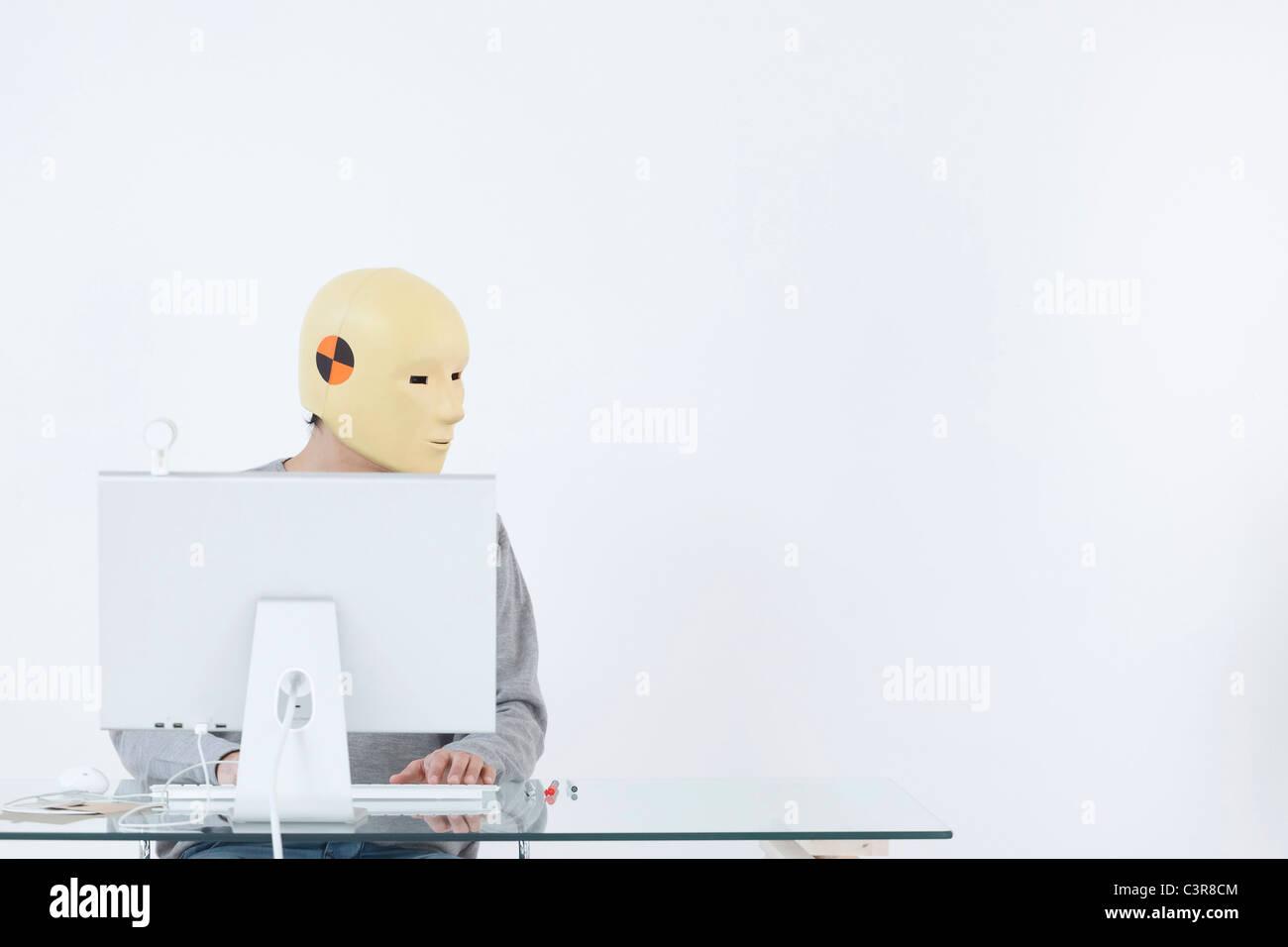 Uomo in crash maschera fittizia lavora al computer Immagini Stock