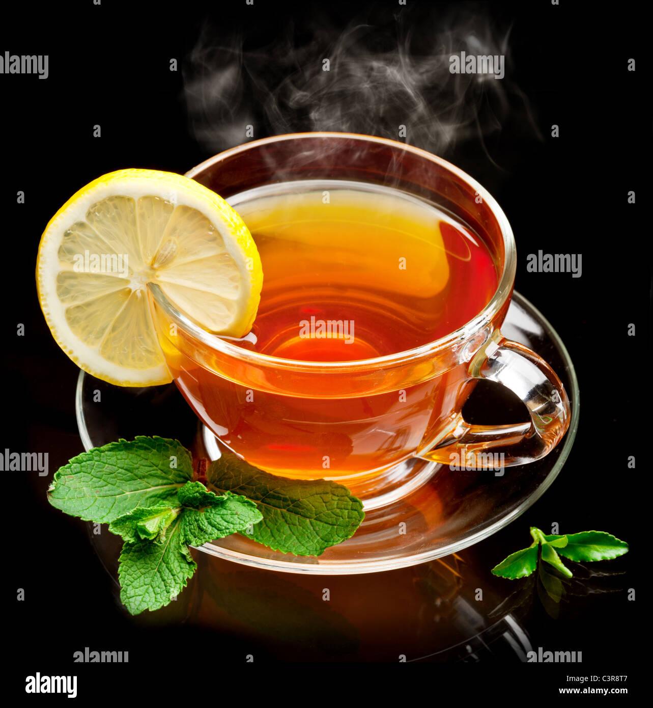 Tazza di tè alla menta e limone isolata su uno sfondo nero. Immagini Stock