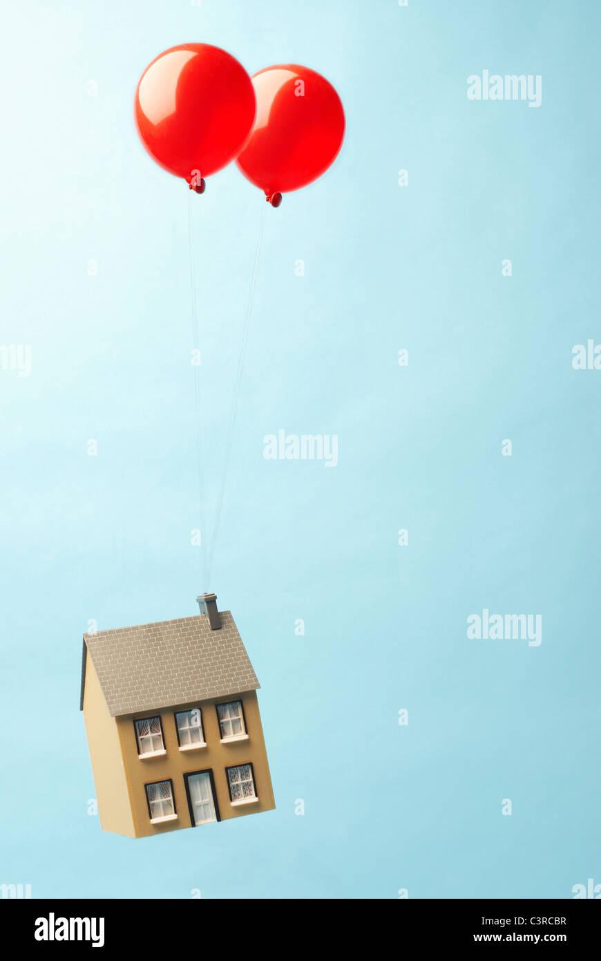 Casa galleggiante di distanza con due palloncini Immagini Stock